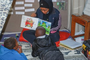 A volunteer reads to children as part of a morning reading workshop.