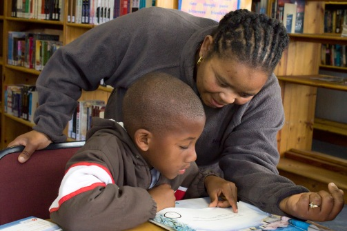 Landie Booi-Mngcambe helps Kamva Mize to pronounce some of the more difficult words in his book at Extension 9 Library, Grahamstown on Wednesday, September 18, 2013. Kamva is a grade 1 learner at Ntaba Maria Primary School. (Photo: Sarah Kingon)