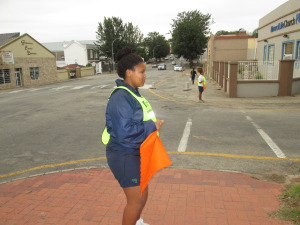 Victoria Girls High School student helping to direct the runners. Photo Credit: Loyiso Gxothiwe.