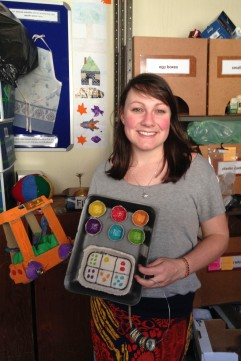 Eyethu administrator, Sarah Larkin holds up a toy car, a maths counter and a musical instrument, all made from waste materials. Photo: Roxanne Daniels