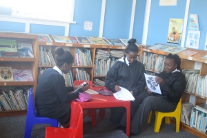 Siphosihle Mzalala, Asemahle Mqina and Lisakhanya Nquru, consult sources for their school project at the Makana Public Library Picture: Ntombovuyo Ngaphu