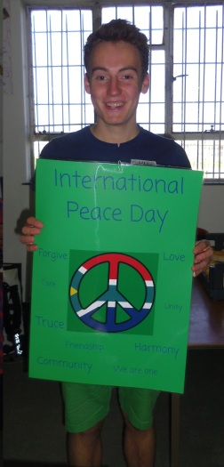 """One of the projects awarenet returns to annually is their International Peace Day celebrations. This year, the learners decided to mark the day by preparing food for those at the Home of Joy orphanage. The staff also created posters to mark the day and its significance – Kim Niemann, one of the two volunteers from Germany, displays with pride the Peace Day poster he made. """"I want awarenet learners to be able to work in teams and take responsibility for their community and their country, learn about their rights and duties as a South African citizen,"""" said Dr Wertlen, who is very proud of all that the previous Peace Day celebrations have achieved. Photo by: Dani Kreusch."""