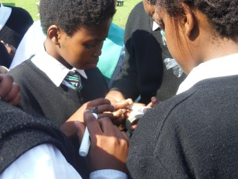 """The awarenet learners carefully write their names on strips of tape that will act as name badges when they go to the Home of Joy. """"Make my name Angelface,"""" one girl pleads, and Siphokuhle Soya, the girl currently with the power of the pen in her hands, rolls her eyes. """"They're not going to worry about your name, when they're grateful for food,"""" she sighs, even as somebody else asks if he can have two name badges, just in case. Photo by: Dani Kreusch."""