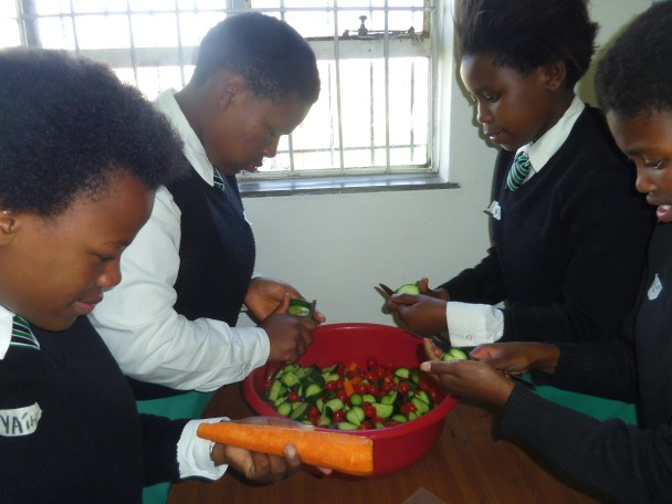 """Siphokuhle and """"Angelface"""" are two of the four assigned the roles of cutting up carrots, tomatoes and cucumber for the meal. """"We want the Home of Joy children to have some vitamins, at least,"""" Larissa laughs. """"This was my idea, because of my love for food,"""" Siphokuhle says solemnly as she cuts a rather stubborn bit of cucumber. Photo by: Dani Kreusch."""