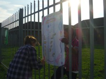 """The last job of the day, as the sun sets lazily, is to put all the Peace Day posters, full of information about human rights and encouraging others to practise Peace Day every day, on the Joza Youth Hub fence. As they work, the awarenet volunteers murmur about the sad stories they've heard that day, and how it's a good thing that their eyes are remaining open. """"Looking is the first step to moving to change,"""" says volunteer Mcvay Bako. Photo by: Dani Kreusch."""